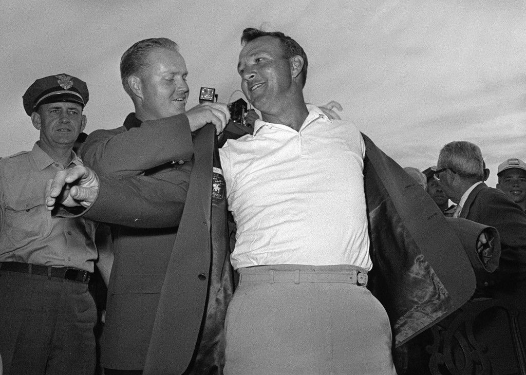 Arnold Palmer, right, slips into his green jacket with help from Jack Nicklaus after winning the 1964 Masters tournament. Palmer, who made golf popular for the masses with his hard-charging style, charisma and  personal touch died Sunday in Pittsburgh. He was 87.     Associated Press