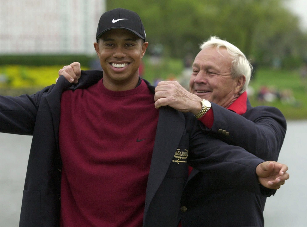 Arnold Palmer puts the green jacket on Tiger Woods after Woods won the 2001 Masters.     Associated Press/Scott Audette