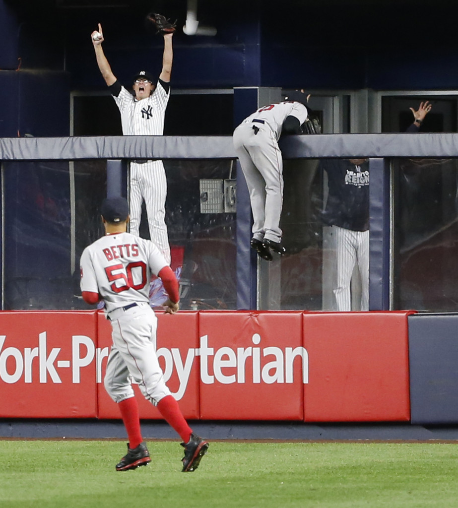 New York Yankees' relief pitcher Tyler Clippard celebrates in the bullpen as Red Sox right fielder Mookie Betts looks on and  center fielder Jackie Bradley Jr. hangs over the bullpen wall after Mark Teixeira's shot clears the wall for a winning grand slam in the ninth inning. Associated Press/Kathy Willens