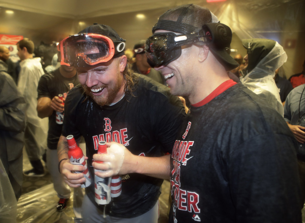Boston Red Sox's Robbie Ross Jr., left, and Aaron Hill, right, celebrate with teammates after the Red Sox clinched the AL East title, following a baseball game against the New York Yankees on Wednesday, Sept. 28, 2016, in New York. (AP Photo/Frank Franklin II)