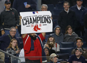A fan of the Boston Red Sox holds up a sign proclaiming them the AL East champions. during the eighth inning of a baseball game between the New York Yankees and the Red Sox in New York, Wednesday, Sept. 28, 2016. The Yankees defeated the Red Sox 5-3, but the Red Sox celebrated after the Toronto Blue Jays lost to the Baltimore Orioles. (AP Photo/Kathy Willens)