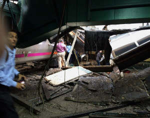 People examine the wreckage of a New Jersey Transit commuter train that crashed into the train station during the morning rush hour in Hoboken,, N.J., on Thursday.