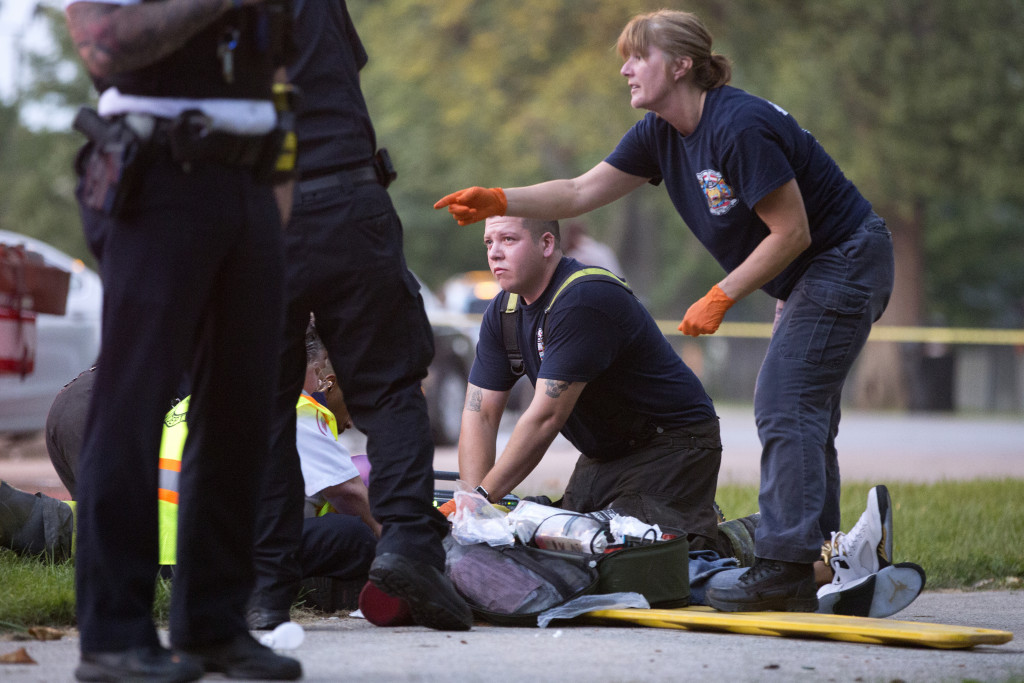 Members of the Chicago Fire Department work on a gunshot victim at the scene of a double shooting on Monday in the Englewood neighborhood of Chicago. Erin Hooley/Chicago Tribune via AP