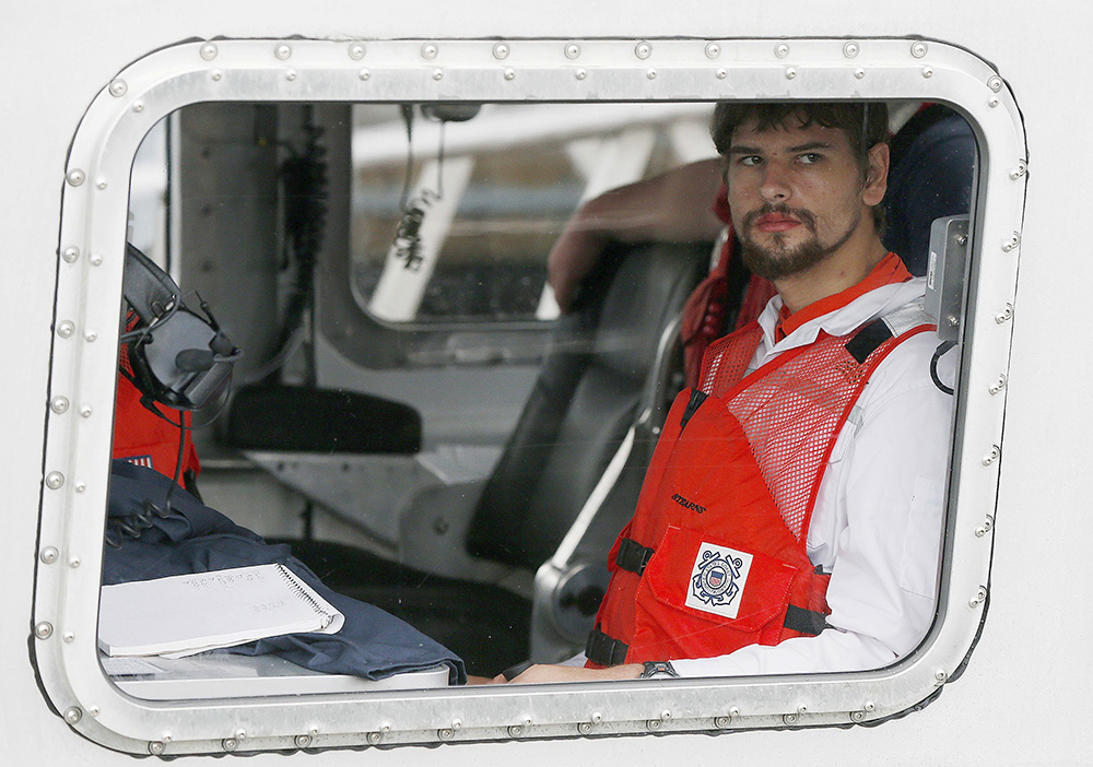 Nathan Carman arrives in a small boat at the U.S. Coast Guard station in Boston Tuesday. Carman spent a week at sea in a life raft before being rescued by a passing freighter. <em>Michael Dwyer/Associated Press</em>