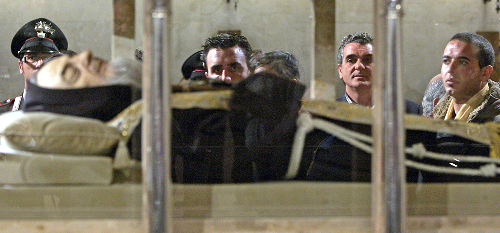 Pilgrims view the body of Padre Pio, an Italian saint, lying in repose inside a crystal casket in the crypt of the church of Santa Maria delle Grazie in San Giovanni Rotondo, Italy, in this 2008 photo. The saint's heart is on display in Lowell, Mass. <em>Gregorio Borgia/Associated Press </em>