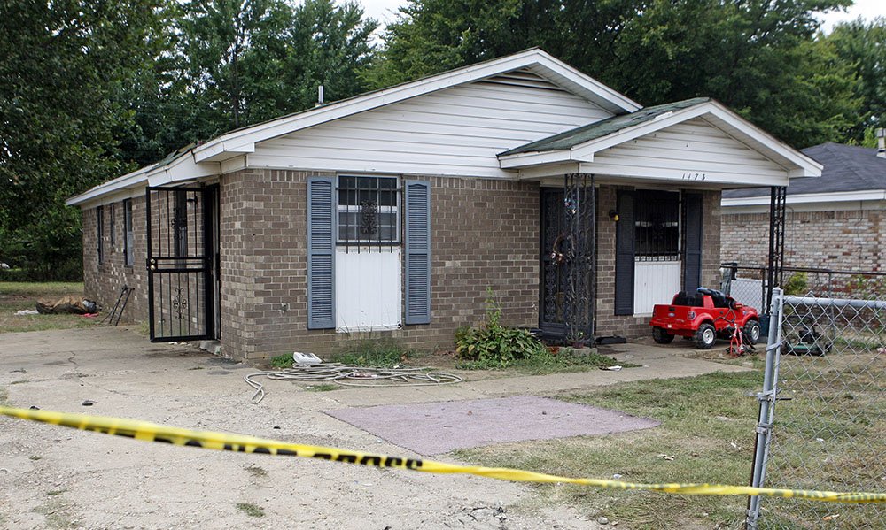 Security tape stretches across the driveway of a home where an early morning fire killed nine people Monday in Memphis, Tenn. <em>Associated Press/Karen Pulfer Focht</em>