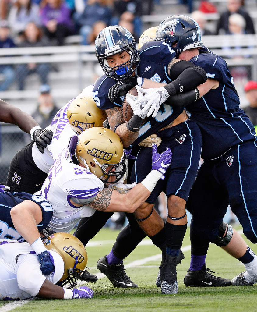 Maine's Darian Davis-Ray fights for extra yardage against James Madison in the first half of action Saturday in Orono.