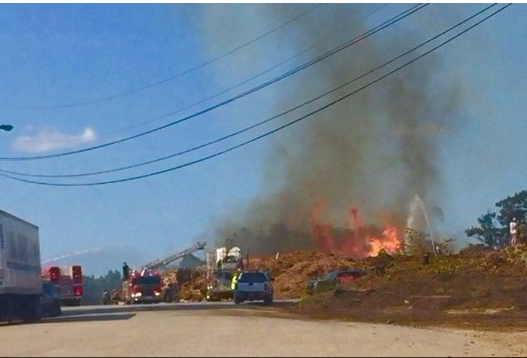 A helicopter dumps water onto a flaming pile of wood chips to help firefighters on the ground at Oldcastle Lawn and Garden in Poland on Sunday. Photo courtesy of WSCH 6