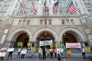 Protesters hold signs outside the new Trump International Hotel on its opening day in Washington Monday. Kevin Lamarque/Reuters