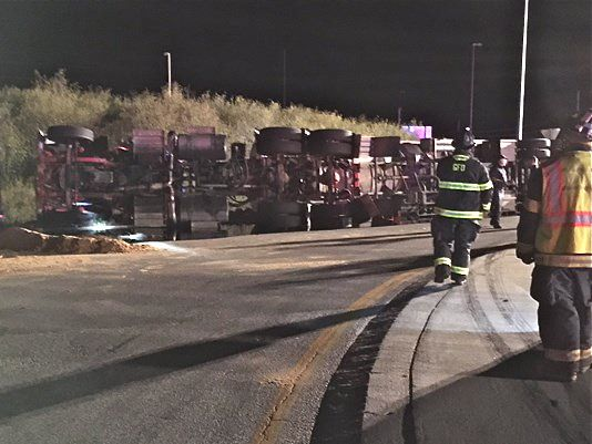 A tractor-trailer tanker truck carrying fuel lies on its side at a rotary in Gorham Thursday night. <em>WCSH photo</em>