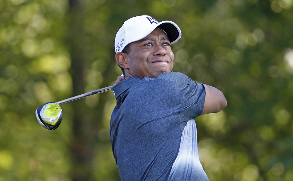 Tiger Woods watches his tee shot on the 13th hole during the Quicken Loans National golf tournament, in Gainesville, Va. , on July 31, 2015. <em>Steve Helber</em>