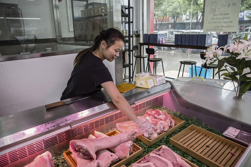 An employee selects a cut of pork for a customer at a retail store operated by the Jia Hua pig farm. Qilai Shen/Bloomberg