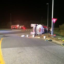 A tractor-trailer tanker truck carrying 5,000 gallons of fuel lies on its side at a rotary in Gorham Thursday night.