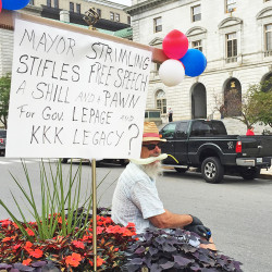Robert Lebel sits on the median in front of City Hall Thursday morning, giving passersby a piece of his mind. Staff photo by John Richardson