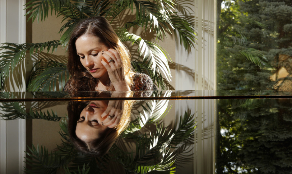 "Kara DioGuardi sits at her piano in her York home. She credits her stint as a judge on ""American Idol"" in 2009 and 2010 with building her confidence and giving her some name recognition, which she hopes to put to good use. ""If I hadn't been on 'Idol' you might not be here now letting me tell people about New England Sings,"" she said, of the upcoming benefit event. Gregory Rec/Staff Photographer"