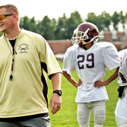 In this Wednesday, Sept. 21, 2016 photo, Algonquin defensive coordinator, Mark Allen, left, son of late Holy Cross Head Football Coach, Dan Allen, works with a squad of Tomahawk players during practice,  Wednesday, Sept. 21, 2016, in Nothboro, Mass. (Steve Lanava/Worcester Telegram & Gazette via AP)