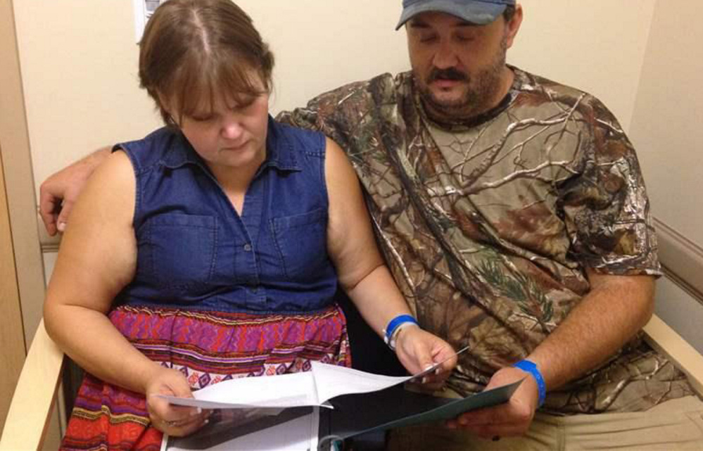 Jillian and Glen Coleman look over schedules at a clinic in Huntington, W.Va. The public favors spiritual-based recovery programs over medications that have proved helpful.