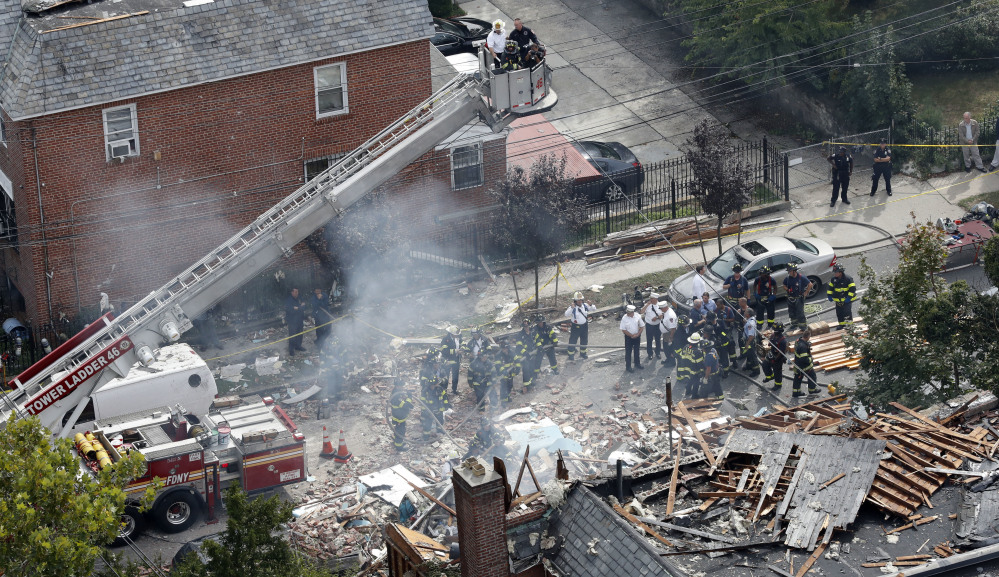 A house smolders Tuesday at the scene of a house explosion in the Bronx borough of New York. Two suspects were arrested on drug charges while officials try to determine if they should face more serious charges after a firefighter died.
