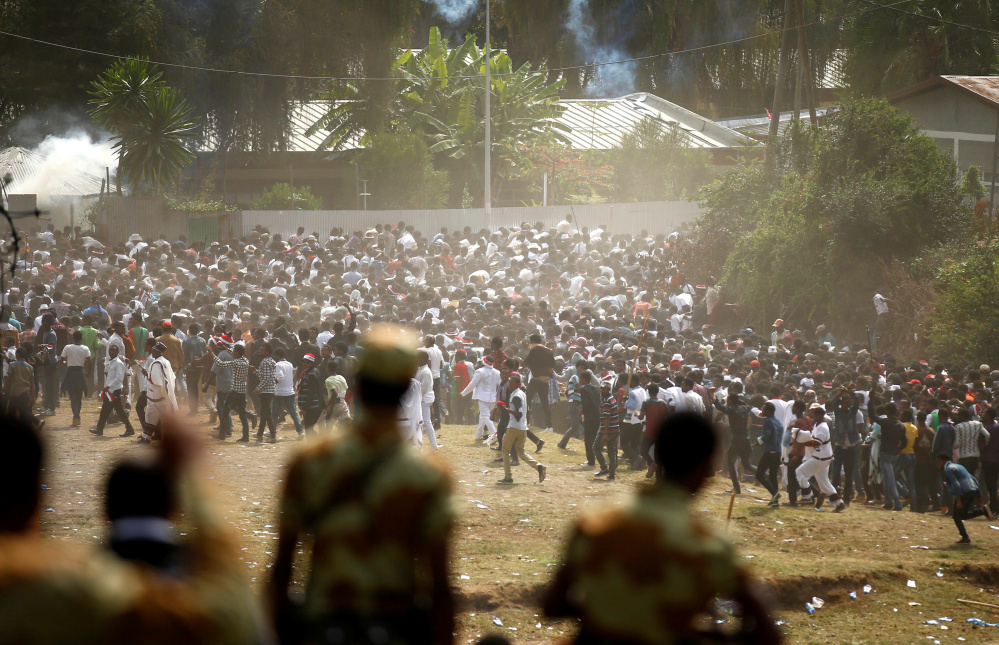 Protesters run from tear gas launched by security personnel during the Irrecha, the thanksgiving festival of the Oromo people, in the town of Bishoftu in the Oromia region of Ethiopia on Sunday.
