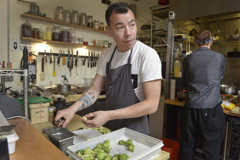 Greenland chef Inunnguaq Hegelund prepares brussels sprouts Monday on the line at Vinland restaurant in Portland. Photos by John Ewing/Staff Photographer