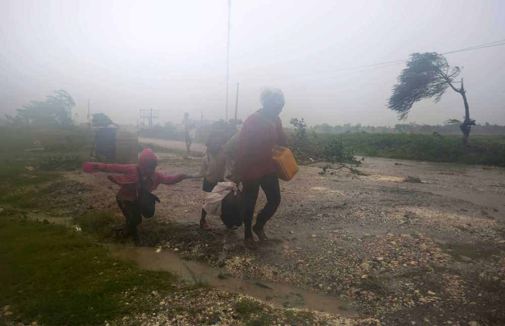 Residents head to a shelter in Leogane, Haiti, on Tuesday as Hurricane Matthew hits.