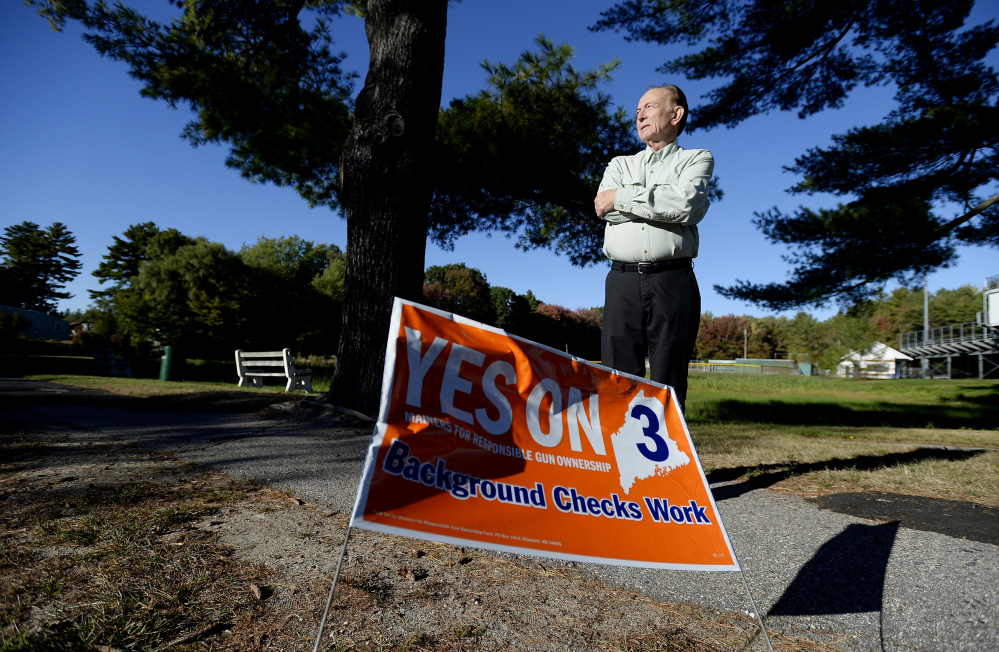 """Bradley Ronco of Portland, who says many of the """"Yes on 3"""" signs in his neighborhood have been knocked down or stolen, stands Wednesday near one of the remaining signs, on Ludlow Street."""