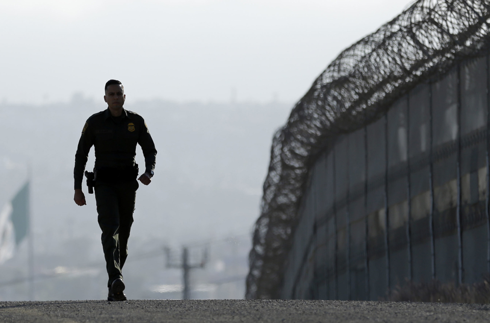 Border Patrol agent Eduardo Olmos walks near the fence separating Tijuana, Mexico, and San Diego.