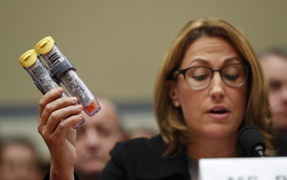 Mylan CEO Heather Bresch holds EpiPens while testifying in Washington on Sept. 21. The Justice Department alleged that the company overbilled Medicaid. Associated Press/Pablo Martinez Monsivais