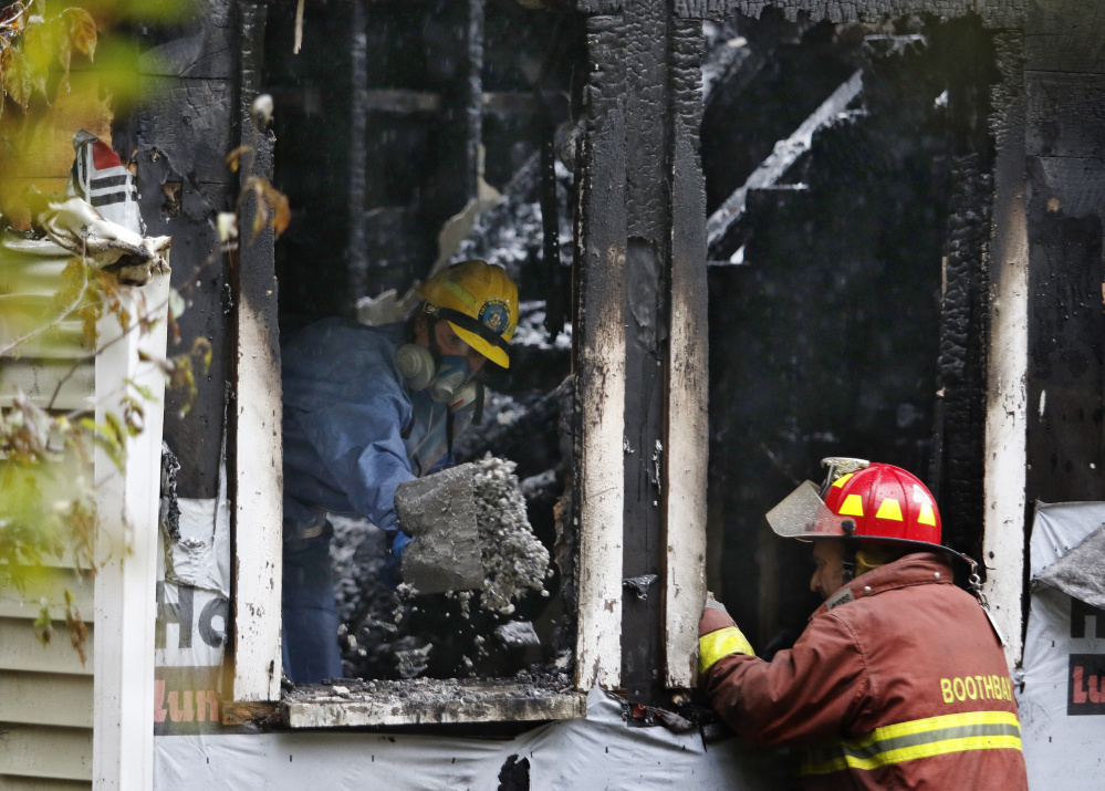 A State Fire Marshal's Office investigator shovels debris out of the house at 116 Pleasant St. in Boothbay following Sunday's fatal fire. One of the four survivors jumped from a second-floor window.
