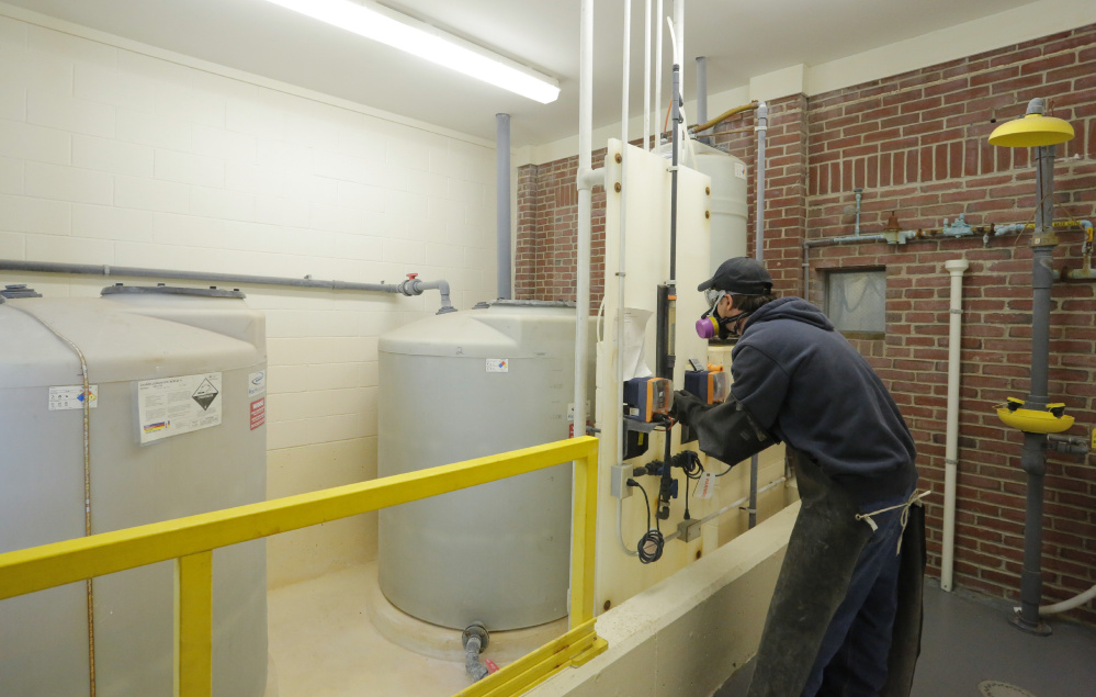 Randy Nichols checks the feed rate of hydrofluorosilicic acid, a type of fluoride, seen in tanks at left, as it is added to water at the Kennebunk, Kennebunkport and Wells Water District. A forum will be held Monday in Kennebunk to discuss an upcoming referendum in seven towns that asks residents if they want to continue to add fluoride to drinking water.