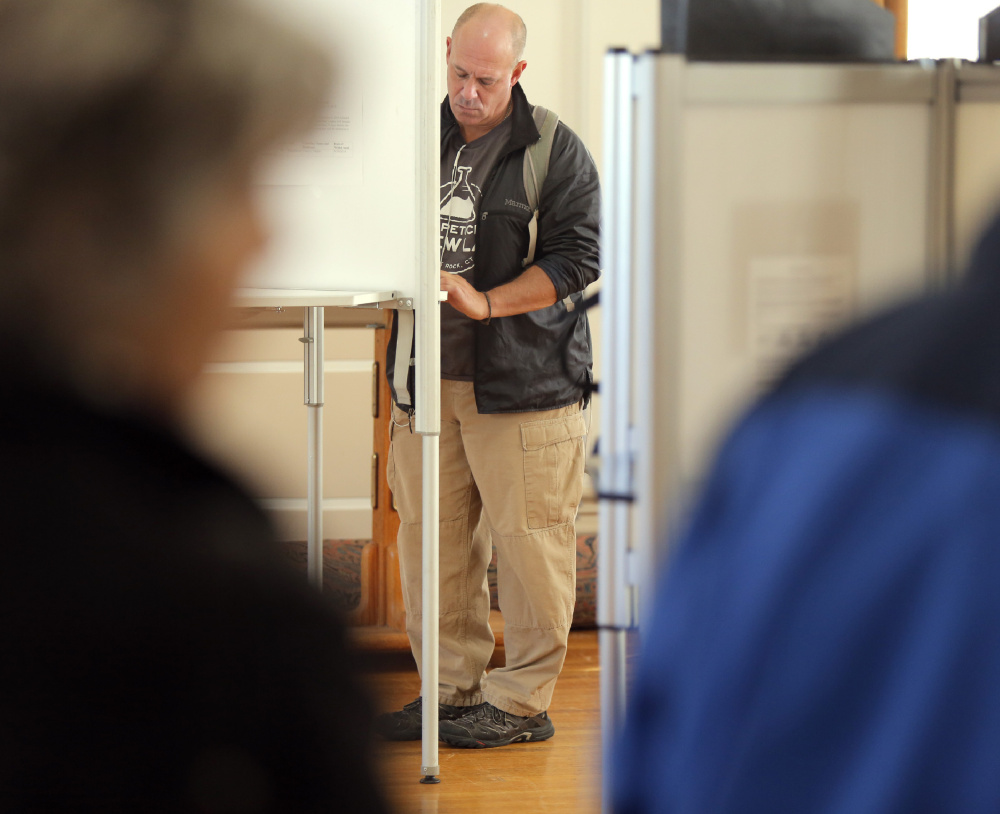 Gregory Seligman votes at City Hall in Portland on Tuesday. Seligman said he felt strongly about voting for Hillary Clinton.