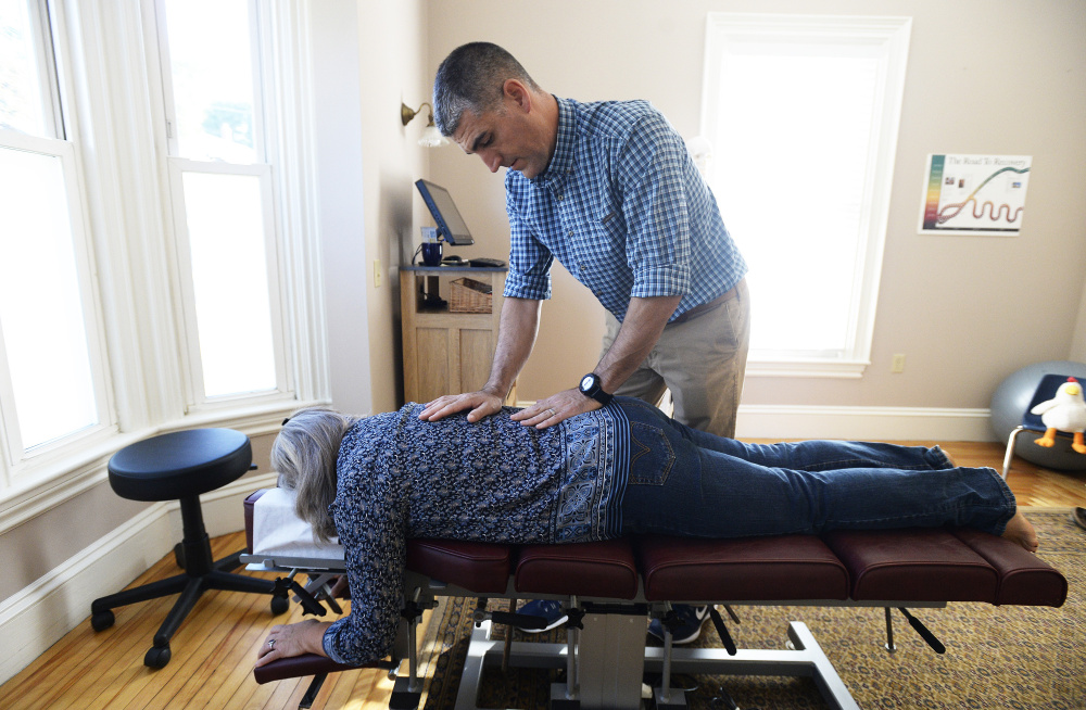 Robert Lavoie makes chiropractic adjustments to a patient, Debra Labbe of Raymond. Back injuries are on the rise for the state's  workers, according to Maine Department of Labor data.