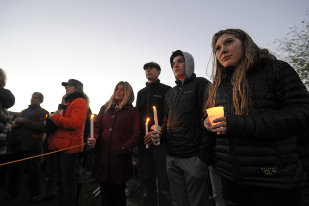 Mourners hold candles during a vigil attended by about 1,000 at Harwood Union High School in Duxbury, Vt., held for the teenaged victims killed in Saturday night's crash on Interstate 89 in Williston.