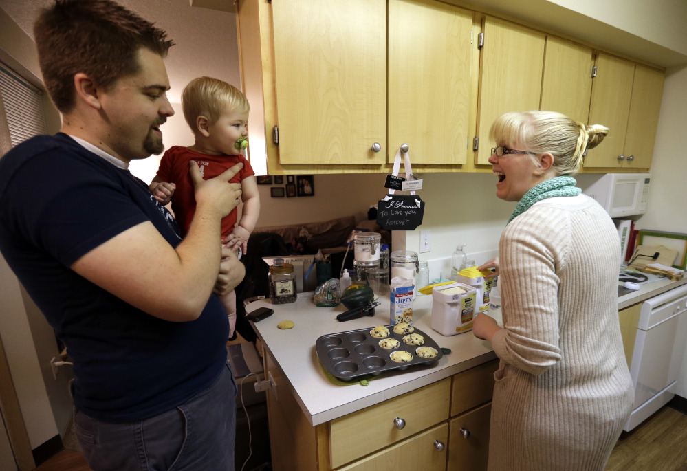 """Shavonne Henry greets her 7-month-old son, Jordan, as her husband brings him into the kitchen. Unlike many of their peers, the Vancouver, Wash., couple in their mid-20s have savings in 401(k) accounts. """"I feel pretty good about our future,"""" said Shavonne."""