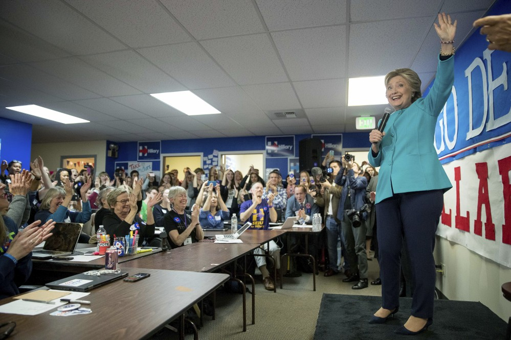 """Hillary Clinton speaks to volunteers Friday at a campaign field office in Seattle. A speech transcript from 2013 in which she cited a need for """"a public and a private position"""" has fed into suspicions that she isn't always straight with voters."""