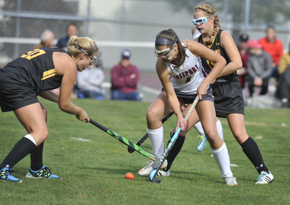 Freeport's Chloe Davidson battles for the ball with Ellie Garfield, left, and Erika Miller of Cape Elizabeth during Saturday's game. Freeport won the Class B South field hockey prelim, 3-0.