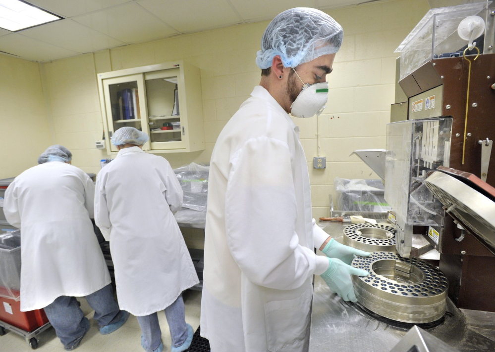 An ImmuCell production associate fills capsules with antibodies used to reduce infections in newborn dairy cattle in this 2011 photo. Maine's smallest publicly traded firm has agreed to sell 660,000 shares to raise capital from private investors for its Portland expansion.