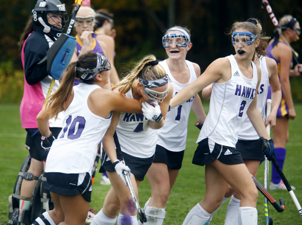 Marshwood High's Elaine Bachelder, left, Hannah Costin and Leah Glidden, right, celebrate a goal by Celine Lawrence in the second half of the Hawks' 4-1 victory over Cheverus in a Class A South field hockey quarterfinal on Tuesday in South Berwick. (Photo by Derek Davis/Staff Photographer)