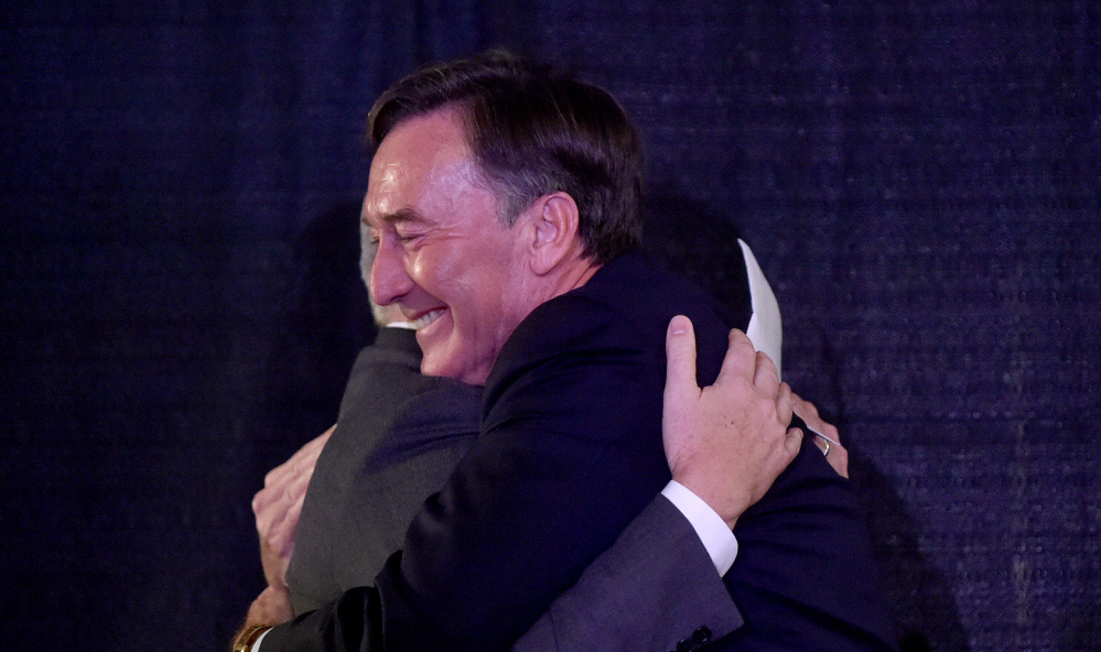 Making no secret of his excitement, Gregory Powell of the Harold Alfond Foundation hugs Colby College's David Greene. The group matched the college's investment in Waterville.