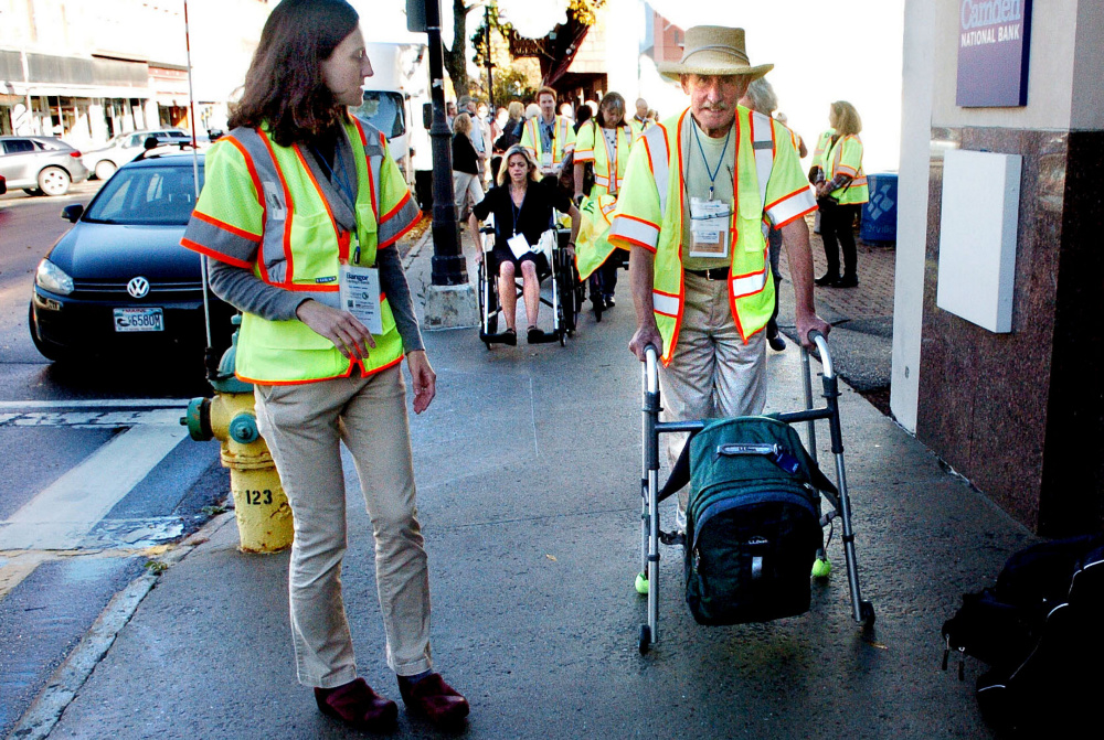 Peter Garrett uses a walker Wednesday as others in wheelchairs navigate sidewalks to illustrate mobility challenges for handicapped people as part of GrowSmart Maine demonstrations in Waterville, where the group held its annual conference. At left is Jill Johanning, an architect and access specialist at Alpha One who monitored the disabilities demonstration.