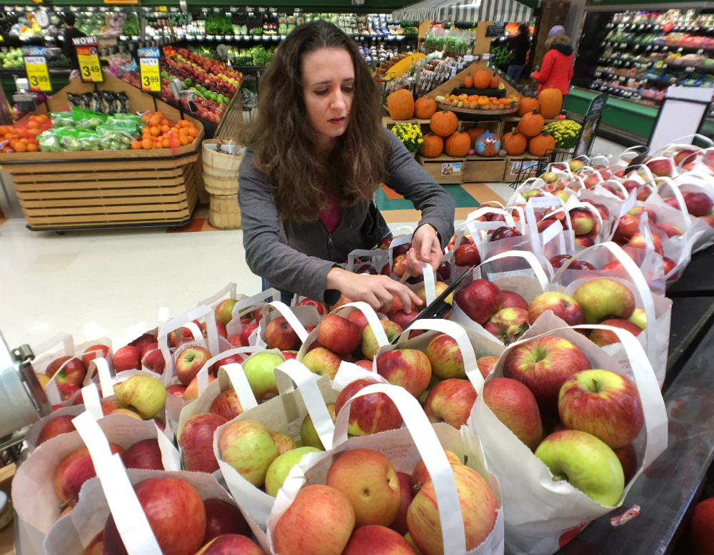 Kati Corlew picks out a bag of apples from Rowe Orchards while grocery shopping at Hannaford in Hampden on Oct. 15. Corlew concentrated on food choices and packaging in her quest to cut down on waste this semester.