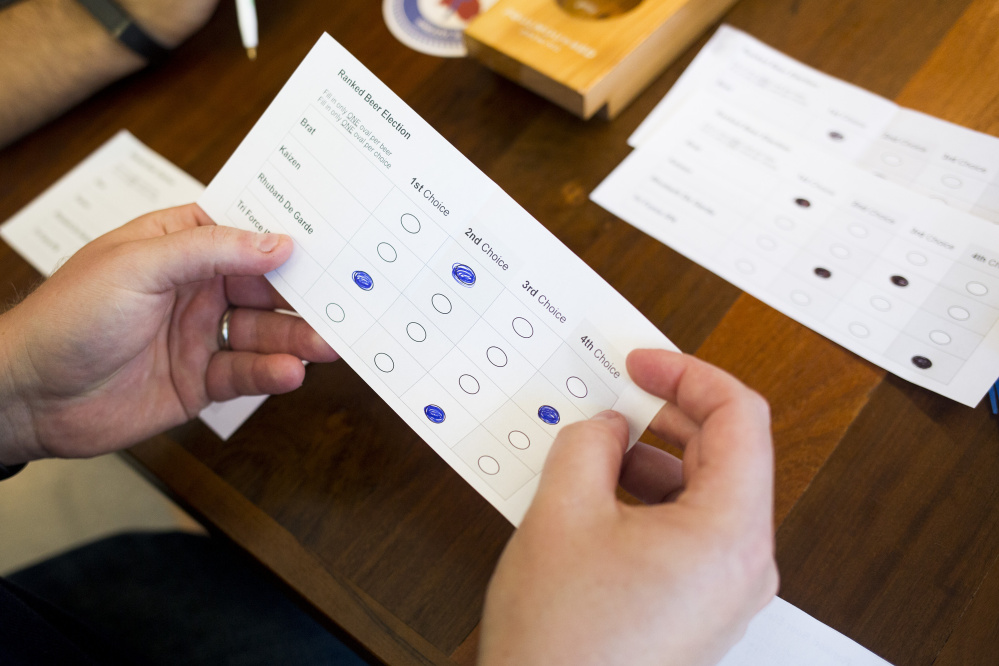 In this October 2016 file photograph, sample ballots  are counted in a demonstration of how ranked-choice voting would work.