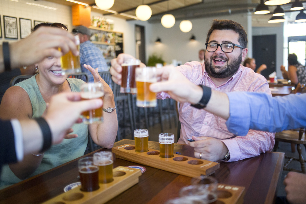 Adam Pontius and others toast ranked-choice voting during a pro-Question 5 demonstration at Foulmouthed Brewing, where participants ranked their favorite beers as a way of showing how voters could rank candidates should the initiative pass on Election Day.