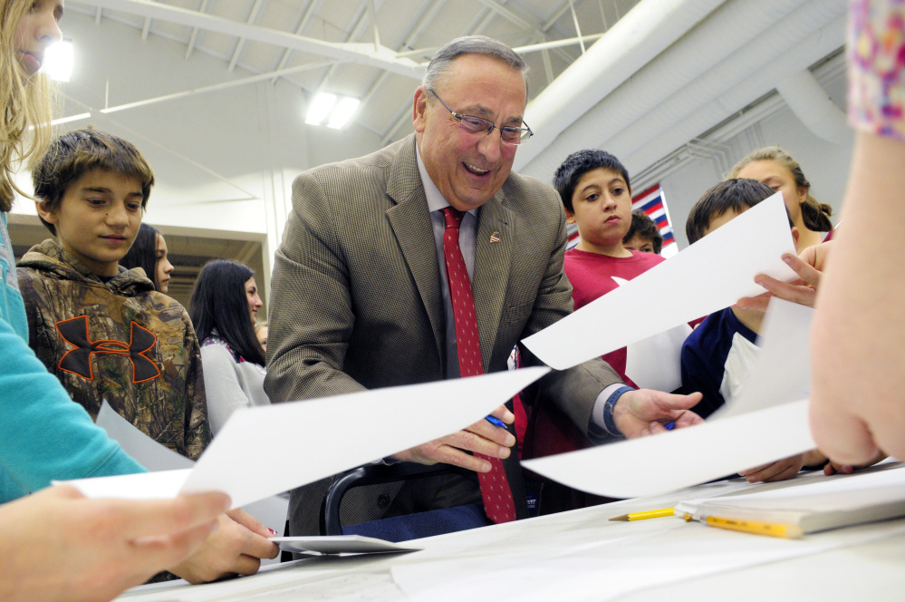Gov. Paul LePage signs autographs for students Wednesday during the mock election event at the Augusta State Armory.