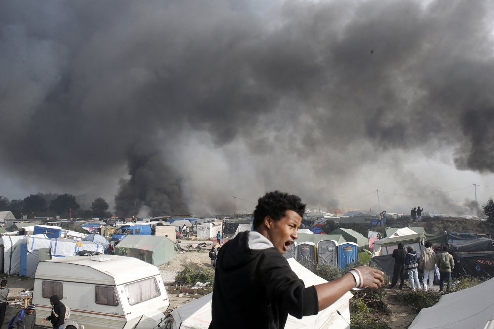 A migrant reacts as smoke billows from burning shelters set on fire in the makeshift migrant camp known as
