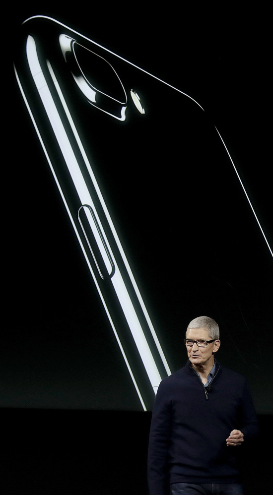 Apple CEO Tim Cook discusses the iPhone, depicted behind him, during an announcement of new products Thursday in Cupertino, Calif.
