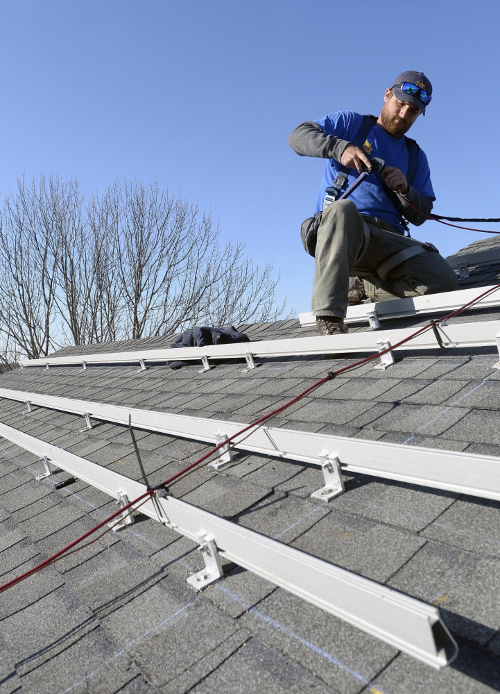 Zach Good of ReVision Energy prepares a roof for solar panels at a home on Overlook Lane in Cape Elizabeth in 2015.