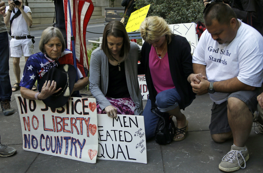 Protestors kneel in prayer outside federal court in Portland, Ore., Sept. 13 as the trial of the Bundy brothers, Ammon and Ryan, and five others gets underway.