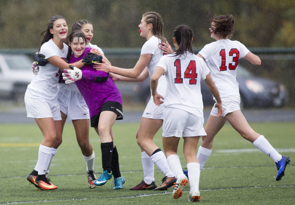 The Scarborough High girls' soccer team celebrates after winning its Class A South semifinal against Windham, 2-0, on Saturday afternoon in Scarborough. (Photo by Brianna Soukup/Staff Photographer)