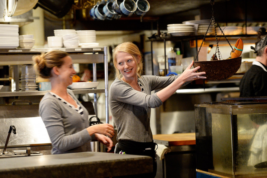 Servers Martina LaChance, left, and Desiree Cofran laugh as LaChance weights a lobster at Boone's Fish House & Oyster Room in Portland on Wednesday. Cofran said a no-tipping policy might work for smaller restaurants, but not high-volume places like Boone's. She said she can make about $30 an hour on average during a shift.